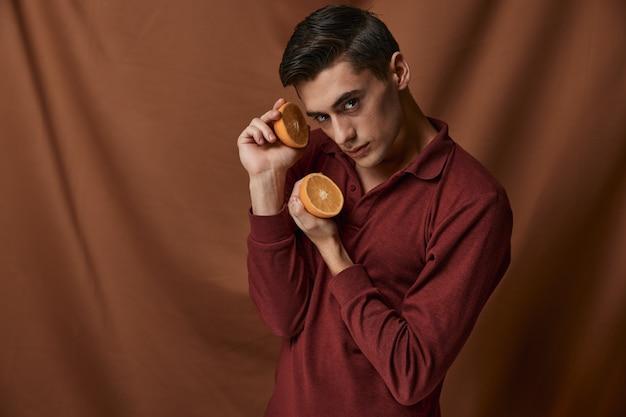 Knappe man rood overhemd sinaasappelen aantrekkelijk kijken model studio.