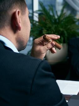 Knappe man rookvrije sigaar in een lounge bar