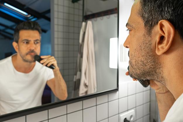 Knappe man scheert zijn baard met trimmer machine voor badkamerspiegel.