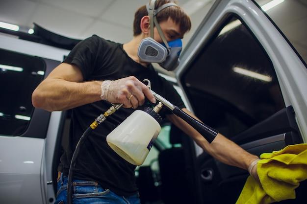 Knappe man schoonmaak auto met hete stoom