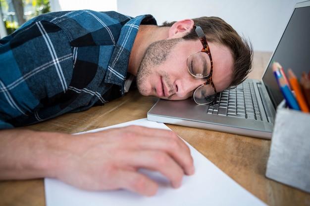 Knappe man slapen op laptop in een heldere kantoor