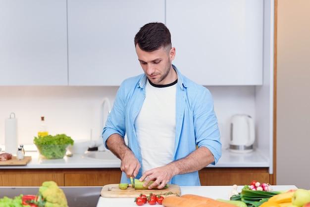 Knappe man snijdt tomaten op een houten bord voor het bereiden van salade van verse groenten in de keuken
