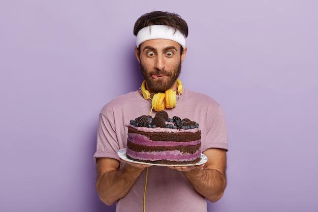 Knappe man staart verrassend naar grote smakelijke cake, likt lippen, heeft een sterk verlangen om een dessert te eten