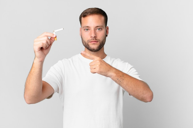 Knappe man stopt met roken met een gebroken sigaar