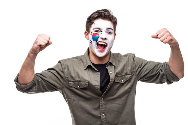 Knappe man supporter fan van het nationale team van de republiek korea met geschilderde vlag gezicht krijgen gelukkige overwinning schreeuwen in een camera. fans van emoties.