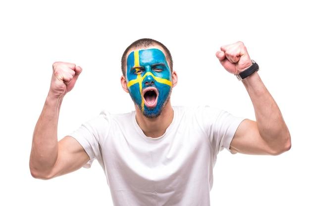 Knappe man supporter fan van het zweedse nationale team met geschilderde vlag gezicht krijgen gelukkige overwinning schreeuwen in een camera. fans van emoties.