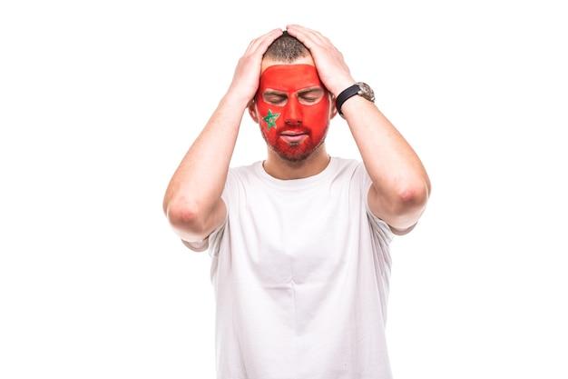Knappe man supporter fan van marokko nationale team geschilderd vlag gezicht ongelukkig verdrietig gefrustreerd emoitions in een camera. fans van emoties.