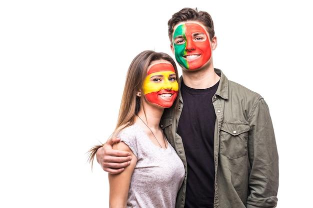 Knappe man supporter fan van portugal nationale team geschilderde vlag gezicht knuffel vrouw supporter fan van spanje nationale team. fans van emoties.