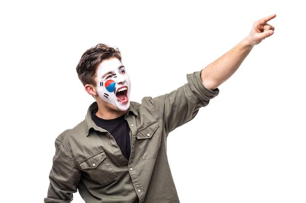Knappe man supporter fan van zuid-korea nationale team geschilderde vlag gezicht krijgen gelukkige overwinning schreeuwende puntige hand. fans van emoties.