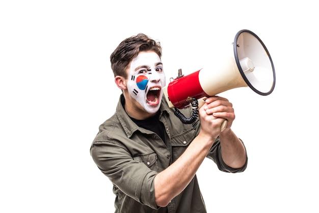 Knappe man supporter loyale fan van zuid-korea nationale team met geschilderde vlag gezicht schreeuwen in megafoon met puntige hand. fans van emoties.
