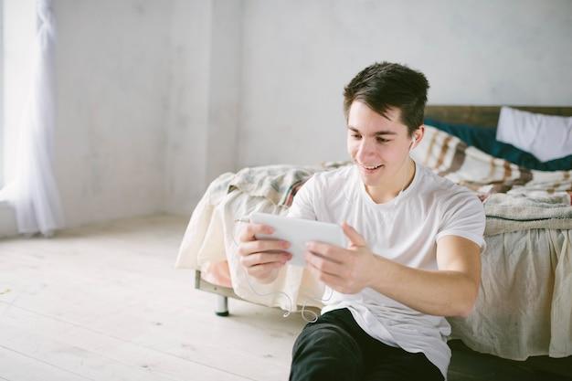 Knappe man surfen op tablet. guy praten met vrienden, videoconferentie, skype, tablet. de jonge student scrollt door sociale netwerken.