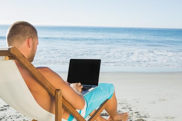 Knappe man te typen op zijn laptop zittend op zijn ligstoel