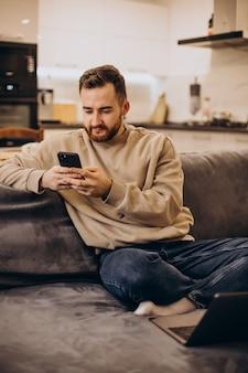 Knappe man thuis op de bank zitten en gadgets gebruiken
