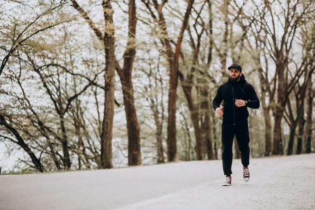 Knappe man uitoefenen in park in sportkleding