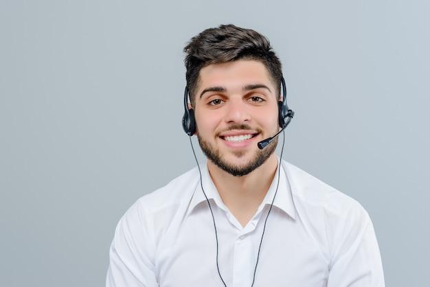 Knappe man van het middenoosten die met hoofdtelefoon werken die bedrijfsgesprekken beantwoorden die als technologieondersteuningsverzender over grijze achtergrond wordt geïsoleerd