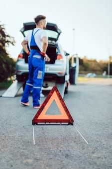 Knappe man van middelbare leeftijd aan het werk in de sleepdienst op de weg. wegenwacht concept.