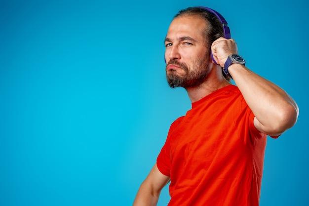 Knappe man van middelbare leeftijd luisteren naar muziek met blauwe koptelefoon portret