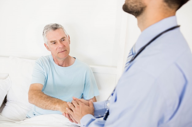 Knappe man verpleegster die hand aan senior man op bed