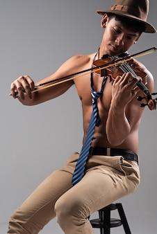 Knappe man viool in de hand houden