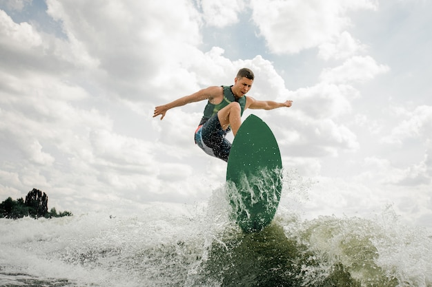 Knappe man wakesurfing op het bord langs de rivier tegen de bewolkte hemel en bomen
