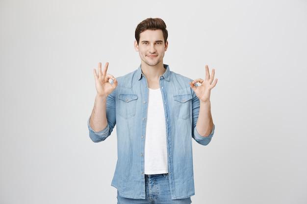 Knappe man zegt geen probleem, toon oke gebaar tevreden