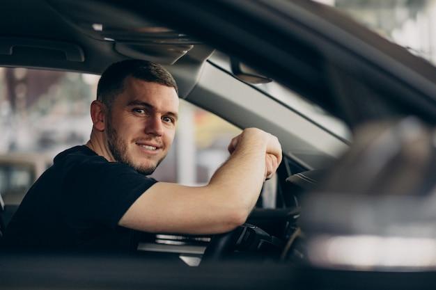 Knappe man zit in de auto en het testen