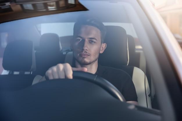 Knappe man zit in een auto en houdt het stuur vast.