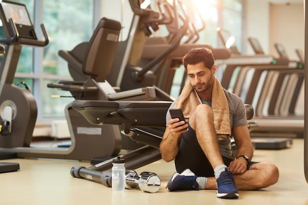 Knappe man zittend op de vloer in de sportschool