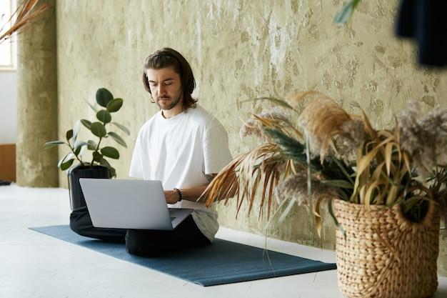 Knappe man zittend op een yogamat en met behulp van laptop, freelance yoga en meditatieleraar werken vanuit huis