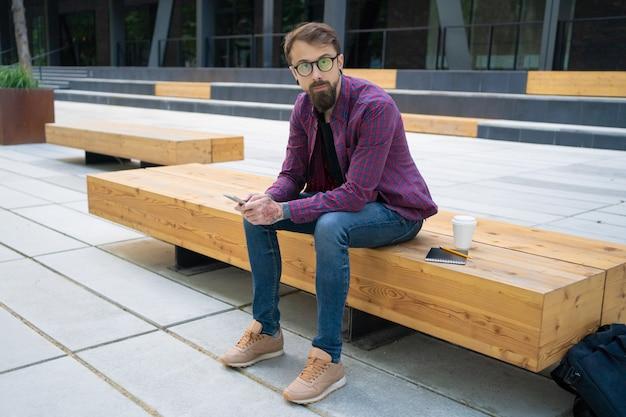 Knappe man zittend op houten bankje met telefoon