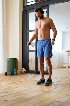 Knappe man zonder shirt die springtouw vasthoudt en glimlacht terwijl hij naar muziek luistert en thuis aan het trainen is