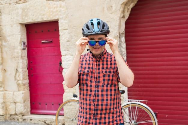 Knappe man zonnebril op de muur steegje en fiets opstijgen.