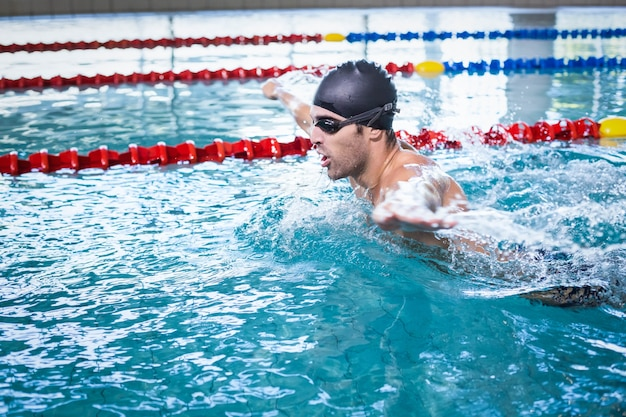 Knappe man zwemmen in het zwembad