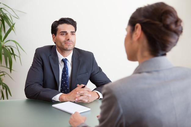 Knappe manager die een vrouwelijke kandidaat interviewt