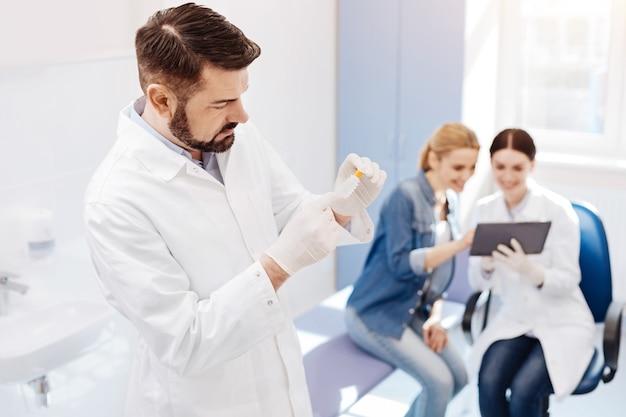 Knappe mannelijke aardige arts permanent in zijn kantoor en houdt een klein speciaal flesje met zijn vrouwelijke collega die met een patiënt werkt