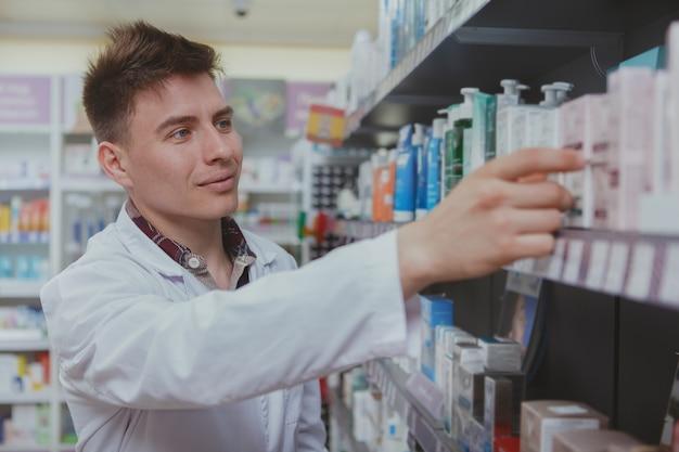 Knappe mannelijke apotheker die bij zijn drogisterij werkt