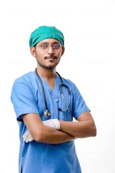 Knappe mannelijke arts die zich op witte achtergrond bevindt.