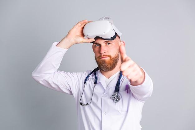 Knappe mannelijke arts op grijze muur in virtual reality-bril