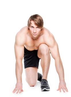 Knappe mannelijke atleet klaar om te rennen - geïsoleerd over een witte muur.