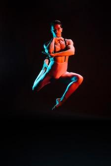 Knappe mannelijke balletdanser die in schijnwerper presteert