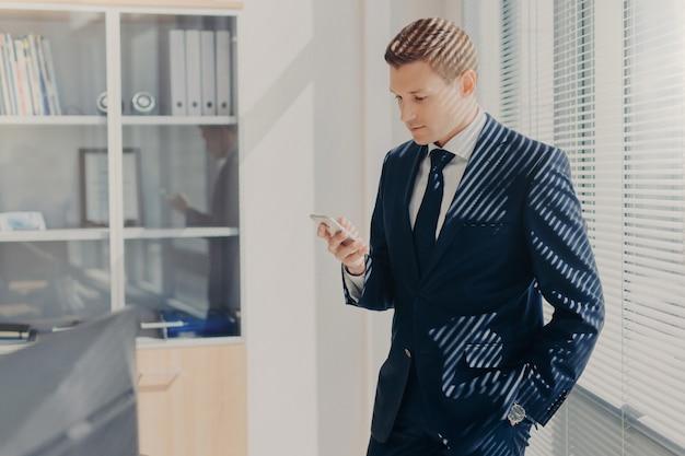 Knappe mannelijke bedrijfseigenaar, leest tekstbericht