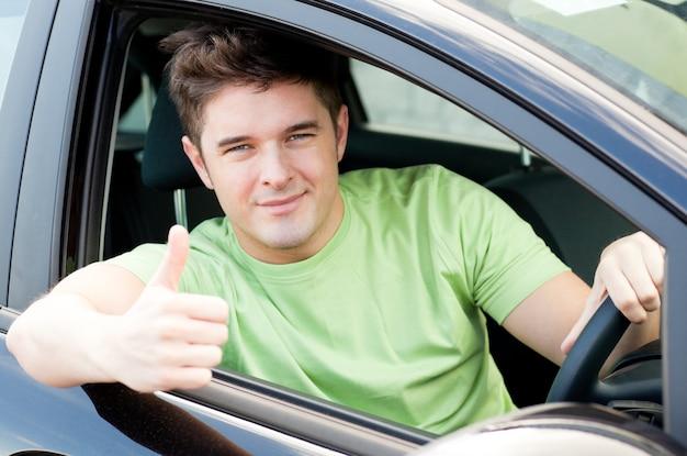 Knappe mannelijke bestuurderszitting in een auto