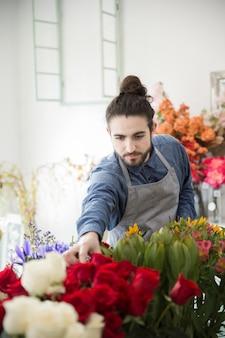 Knappe mannelijke bloemist oppakken van de roos van boeket