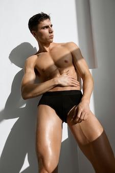 Knappe mannelijke bodybuilder in donkere korte broek opgeblazen lichaam onderaanzicht