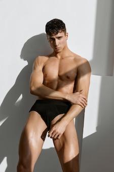 Knappe mannelijke bodybuilder met gespierd lichaam die zwart slipje stapelt