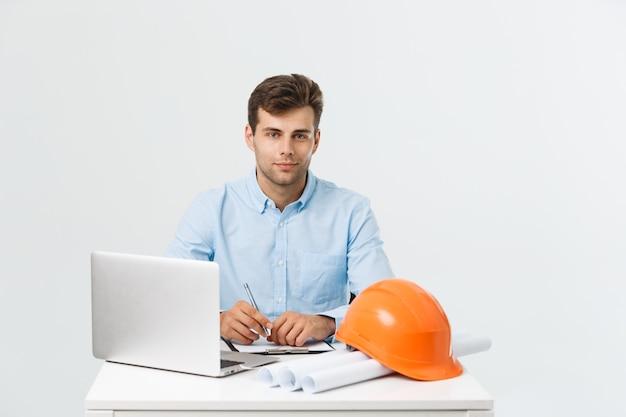 Knappe mannelijke bouwingenieur die met laptop op kantoor werkt