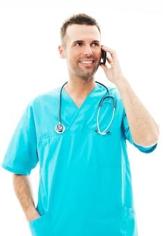 Knappe mannelijke chirurg praten op een mobiele telefoon