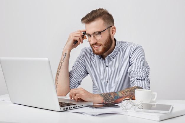 Knappe mannelijke copywriter werkt aan een nieuw artikel, leunt met de elleboog op het bureau, gebruikt laptop, slimme telefoon,