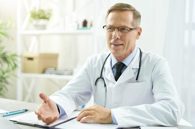 Knappe mannelijke dokter zit aan de tafel in zijn kantoor