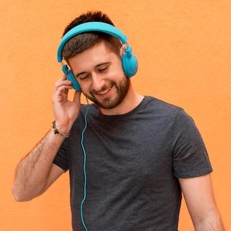 Knappe mannelijke het luisteren muziek in hoofdtelefoons
